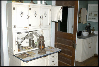The kitchen inside the house, lit only by gas light